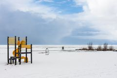 Snowy beach near a frozen sea with a playground for children Stock Image