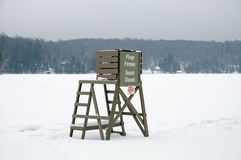 Snowy beach scene. The life savers chair is the only reminder of summer Stock Image