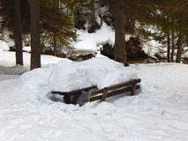 Snowy bench. Near by a river in the Alps Royalty Free Stock Photography