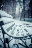 Snowy bench in the park in winter. Retro look Stock Photos