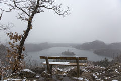 Snowy bench with a view on island in the middle of Lake Bled. Stock Images