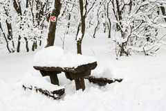 Snowy benches and red bike sign Royalty Free Stock Photos