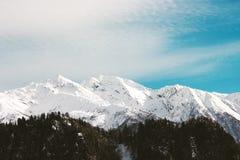 Snowy-Berge und blauer Himmel mit Wolken Stockfotos