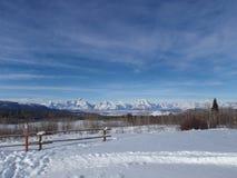 Snowy-Berge und -Bretterzaun Stockfoto