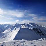 Snowy-Berge und Sonnenlichthimmel lizenzfreies stockbild