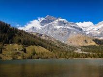 Snowy-Bergspitze hinter einem alpinen See stockbild