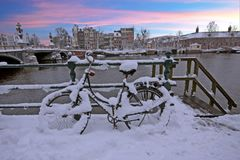 Snowy bicycle in Amsterdam city center the Netherlands. At sunset Royalty Free Stock Photography