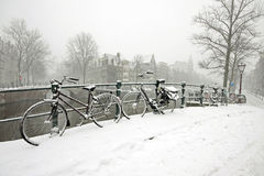 Snowy bikes in Amsterdam the Netherlands. Snowy bikes in Amsterdam innercity in the Netherlands Stock Photo