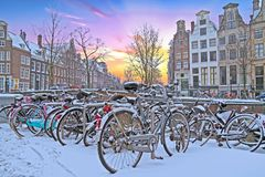 Snowy bikes in Amsterdam the Netherlands. Snowy Amsterdam in the Netherlands in winter at sunset Royalty Free Stock Images