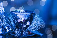 Snowy Blue Background With Hat And Silver Christmas Bells Abstra. Ct Bokeh. Selective Focus With Copy Space Royalty Free Stock Photos