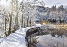 Snowy-Brücke über dem Teich Stockfoto
