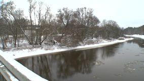 Snowy bridge and ice floe flow on river water in winter. Panorama shot stock video