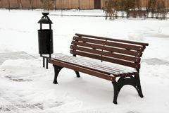 Snowy brown garden bench in the park. Royalty Free Stock Photo