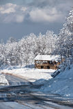 Snowy cabin by the road Royalty Free Stock Photos