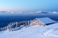 Snowy cabin in the winter mountains Royalty Free Stock Image