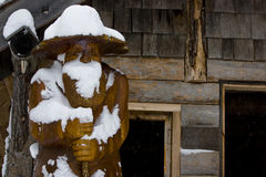 Snowy cabin in the woods. Snow piles up deep on a wooden carving during a winter storm Stock Photo