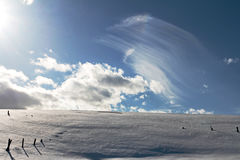 A snowy cattle fence under white-blue sky Stock Photography