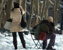 Snowy Cell Phones. Man and woman on cell phones in a snowy park.  The man is sitting.  They are both holding bags Stock Photos