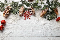 Snowy christmas background with fir branch and pine cones. Stock Photography