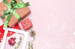 Snowy Christmas composition. White photo frame, red envelope, fir branches, cones ball twine gift wooden toys on pink background. Flat lay top view Christmas stock image