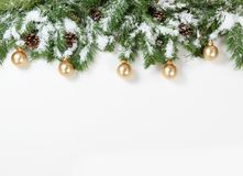 Snowy Christmas gold ornaments hanging in fir tree branches Stock Photo