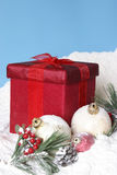 Snowy Christmas Pines Baubles and Gift Box Royalty Free Stock Photography