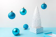 Snowy Christmas tree with Christmas decoration on blue table. Christmas or New Year minimal concept.  stock photo