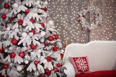 Snowy Christmas tree with red gifts decoration and comfy sofa be. Fore bokeh lights on the wall in holiday room interior home Stock Photo