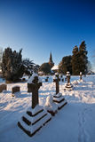 Snowy churchyard on a bright winter afternoon Stock Photos