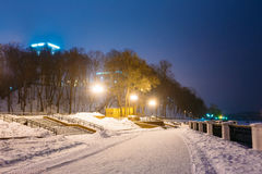 Snowy city park in light of lanterns at evening in Gomel, Belaru Royalty Free Stock Images