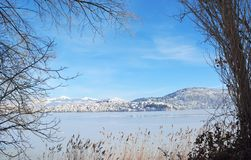 Snowy cityscape with frame from bare branches. Lake Orestiada and town of Kastoria in Greece covered with snow and frame from bare branches royalty free stock photos