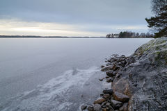 Snowy cliff at a shore and frozen lake in the winter Royalty Free Stock Photography
