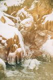 Water flows over a partially frozen Upper Cataract Falls in rural Indiana. Royalty Free Stock Photo