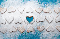 Snowy cookie-hearts in lines with an empty heart in the middle Stock Photography