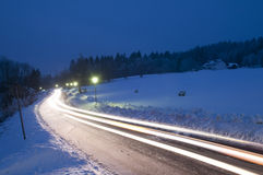 Car trail in night winter road. Snowy country road with lightbeams at dusk Royalty Free Stock Photos