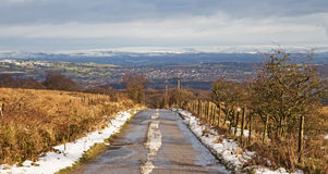 A snowy country road looking towards  high, snow covered moors in the background Royalty Free Stock Photography