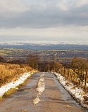A snowy country road looking towards snow covered moors in the background Royalty Free Stock Photos