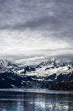 Snowy covered mountains by lake Stock Photography