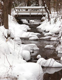 Snowy Creek and Bridge. A creek running through snow covered rocks and a bridge covered with snow Stock Images