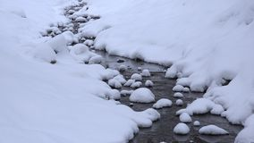 Snowy creek water flow in winter park channel. Snow fall. Zoom in. 4K. Snowy creek water flow in winter park channel. Snow fall blizzard. Zoom in shot. 4K stock video