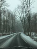 Snowy Curve Up Ahead. Driving on snowy roads, with curve up ahead from drivers perspective stock image