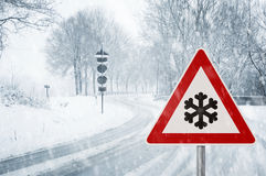 Snowy curvy road with traffic sign Stock Images