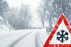 Snowy curvy road with traffic sign Royalty Free Stock Image