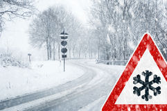 Snowy curvy road with traffic sign Stock Photography