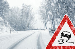 Snowy curvy road with traffic sign Royalty Free Stock Images