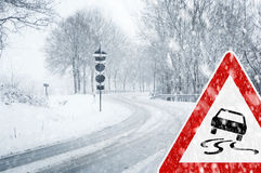 Snowy curvy road with traffic sign Royalty Free Stock Photography