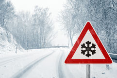 Snowy curvy road with traffic sign Royalty Free Stock Photos