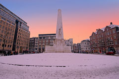 Snowy Damsquare in Amsterdam Netherlands at sunset Stock Photo