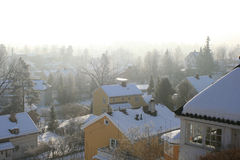 Snowy day. It is snowing lightly over the trees and houses stock image