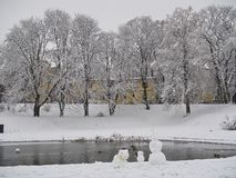 Snowy day in the park. Corner of the pond snowman family sculptu stock image